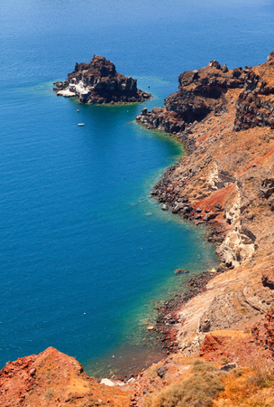 waters: A perfect view of the volcano in Oia, Santorini with blue waters of the sea. Vertical shot