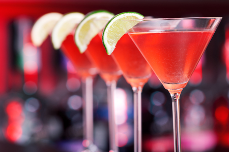 martini shaker: Row of Cosmopolitan cocktails shot on a bar counter in a nightclub. Shot in red light.
