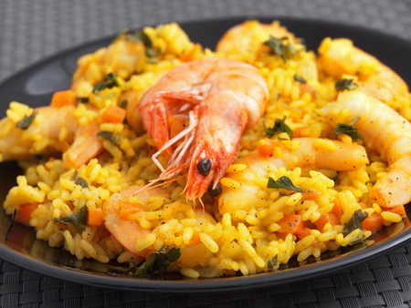 Seafood risotto with shrimps, curry and herbs. Horizontal shot, macro