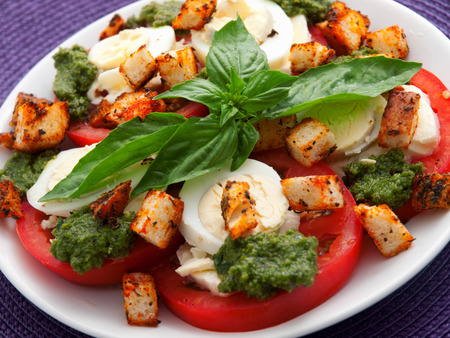 boiled eggs: Healthy salad with tomatoes, boiled eggs, pesto and croutons. Close up, horizontal view Stock Photo