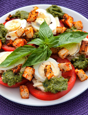 boiled eggs: Healthy salad with tomatoes, boiled eggs, pesto and croutons. Vertical shot