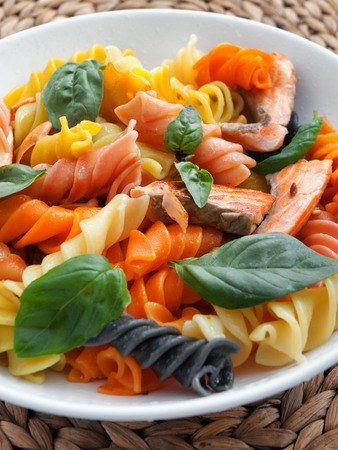 fusilli: Colorful fusilli pasta with baked salmon and basil. Vertical shot