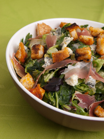 tilted view: French Provencal Salad with green salad, bacon, croutons and blue cheese. Tilted view, vertical shot