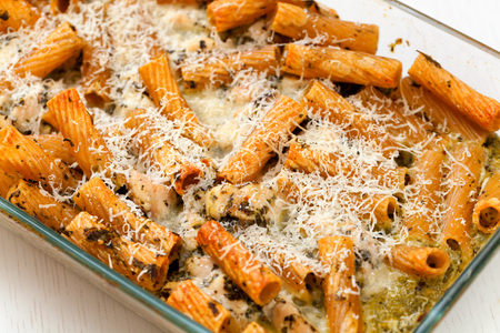 tilted view: Baked Penne pasta with parmesan cheese in caserole. Shot from above. Tilted view, horizontal shot Stock Photo