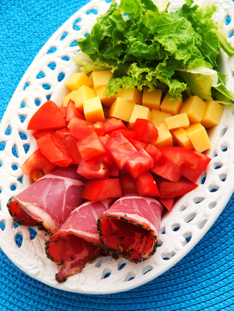 hams: Healthy breakfast with prosciutto, tomatoes, yellow cheese and salad. Vertical shot