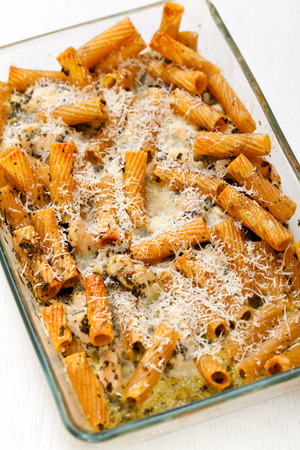 tilted view: Baked Penne pasta with parmesan cheese in caserole. Shot from above. Tilted view Stock Photo