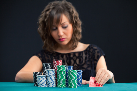 holdem: Young woman with a pile of gambling chips, looking her cards while playing texas holdem poker