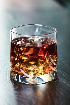 whiskey on the rocks: Whiskey on the rocks on a table. Shallow depth of field.