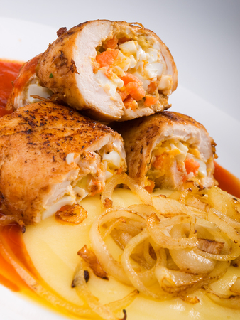 potatoe: Chicken roulades stuffed with boiled eggs, carrots and onion. Tomato and potatoe puree for side dish. Vertical shot