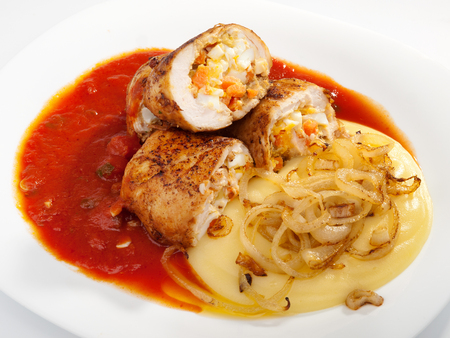 potatoe: Chicken roulades stuffed with boiled eggs, carrots and onion. Tomato and potatoe puree for side dish. Horizontal shot
