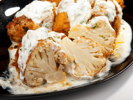 tilted view: Fried Cauliflower with yogurt garlic sauce. Close up, tilted view