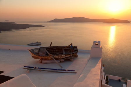 firostefani: Old boat on the roof of a building in Firostefani, Santorini. Shot at sunset. The volcano on background. Horizontal shot Stock Photo
