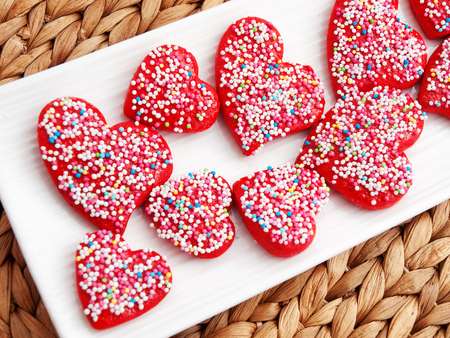 tilted view: Homemade heart-shaped red cookies decorated with colorful sprinkles. Tilted view.
