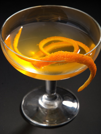 vermouth: Satan Whiskers cocktail isolated on black background. Made from 1 oz gin, 12 oz orange liqueur, 1 oz dry vermouth, 1 oz sweet vermouth, 1 oz orange juice, 2 dashes orange bitters Stock Photo