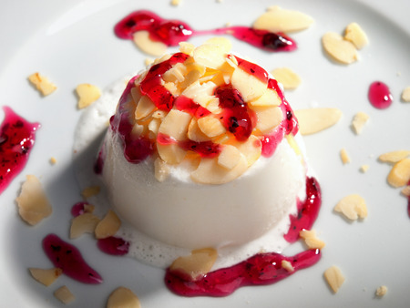 Bavarian jelly cream, topped with almonds and raspberry jam. Horizontal shot