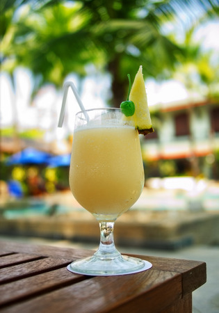 pina colada: Yellow Pina Colada cocktail on a table on tropical island. Palm trees on background Stock Photo