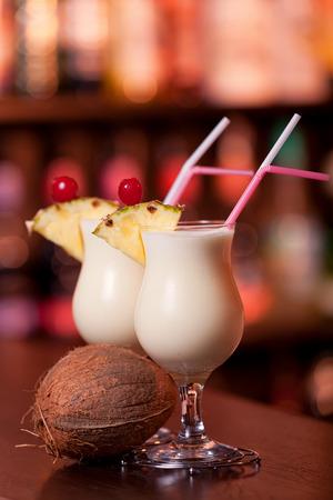 colada: Pina Colada cocktails shot in a bar in dim light.