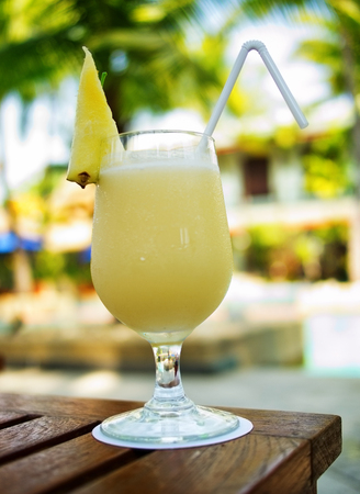 colada: Yellow Pina Colada cocktail on a table on tropical island. Palm trees on background Stock Photo