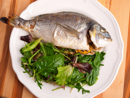 sea bream: Baked sea bream with green salad shot from above