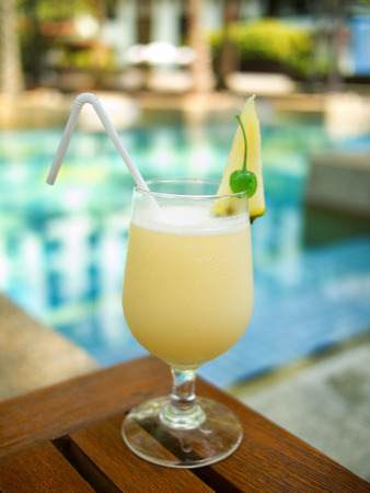 pina: Pina Colada cocktail on a table on tropical island. Palm trees on background Stock Photo
