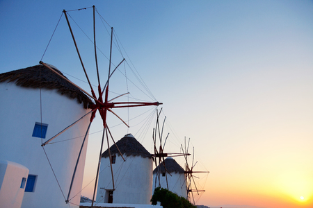 mykonos: Row of windmills in front of a blue sky in Mykonos island, Greece at sunset.