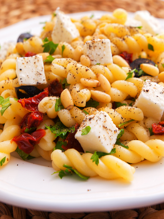 fusilli: Fusilli pasta with feta cheese, dried peppers and parsley. Close up