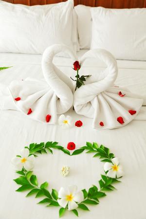 honeymoon suite: Towel swan heart on the bed - special honeymoon hotel decoration