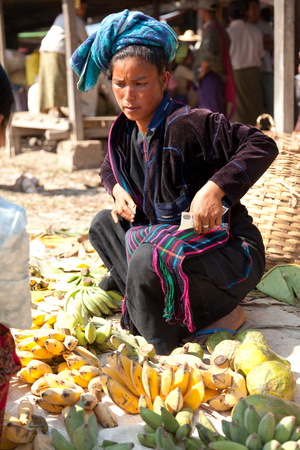 sitting on the ground: Heho, Myanmar - March 02, 2011 - Senior Burmese woman selling bananas at five-day market while sitting on the ground