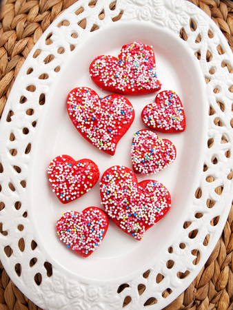 heartshaped: Homemade heart-shaped red cookies decorated with colorful sprinkles. Shot over wooden background