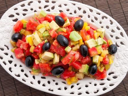 Gesunder Salat mit Avocado, Tomaten, Oliven und grüne Paprika