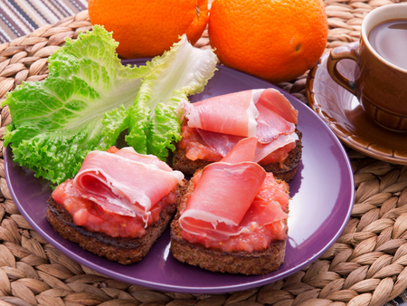hams: Toasts with prosciutto and tomatoes salsa. Decorated with cup of coffee and oranges. Horizontal shot