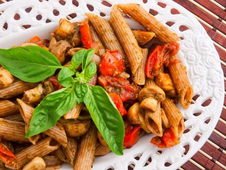 whole wheat: Whole wheat penne pasta with tomatoes and basil. Horizontal shot Stock Photo