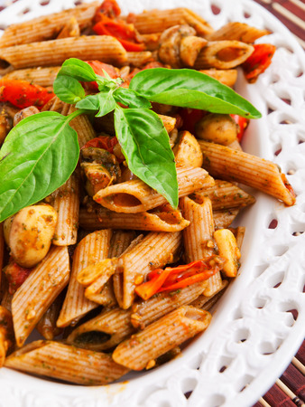 whole wheat: Whole wheat penne pasta with tomatoes and basil.Vertical shot Stock Photo