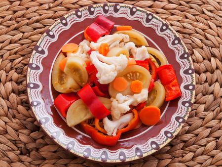 coliflor: Encurtidos de tomates verdes, zanahorias, zanahorias y coliflor. Disparo desde arriba