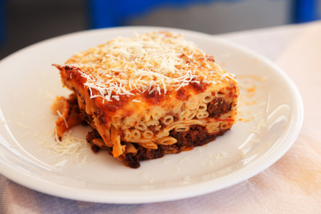 taverna: Traditional greek pasta called pastitsio on white plate in a restaurant Stock Photo