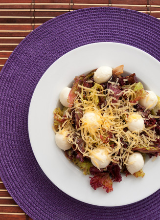 grated mozzarella cheese: Red romain salad with grated cheese and baby mozzarella balls. Vertical shot