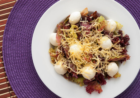grated mozzarella cheese: Red romain salad with grated cheese and baby mozzarella balls. Horizontal shot Stock Photo