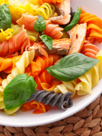 fusilli: Colorful fusilli pasta with baked salmon and basil. Close up, vertical shot Stock Photo