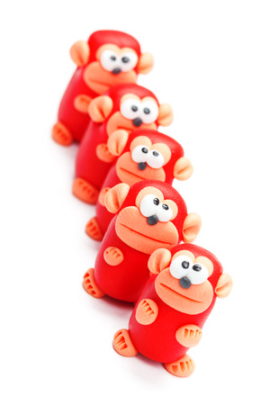 Row of clay toys (monkeys). Isolated on white background, tilted
