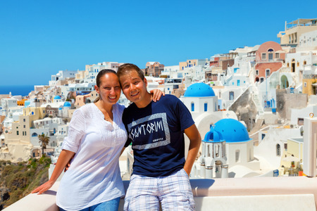Portrait of happy couple with cityscape of Oia, Santorini on background