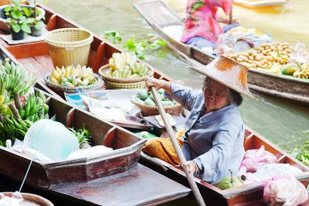 saduak: Damnoen Saduak, Thailand - March 21, 2011 : Senior Thai woman with hat selling fresh fruits on a boat in Damnoen Saduak Floating Market