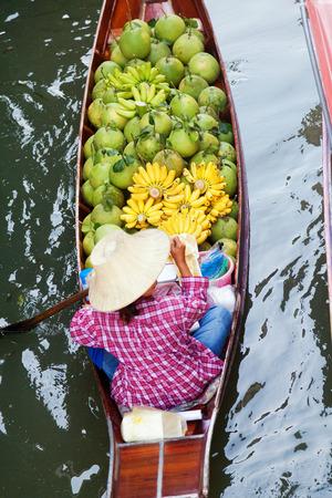 saduak: Damnoen Saduak, Thailand - March 21, 2011 : Senior Thai woman with a hat on a boat full of fruits in Damnoen Saduak Floating Market Editorial