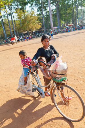 Angkor Wat, Cambodia - March 19, 2011 : Cambodian woman driving her small child and her baby on a bike while trying to sell goods to the tourists that come to see Angkor Wat