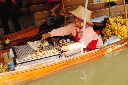 saduak: Damnoen Saduak, Thailand - March 21, 2011 : Young Thai woman selling freshly cooked food and fruits on a boat in Damnoen Saduak Floating Market