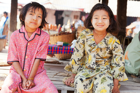 Heho, Myanmar - March 02, 2011 : Two Burmese girls wearing facial herb make up called thanaka, shot at five day market near Inle Lake Editorial