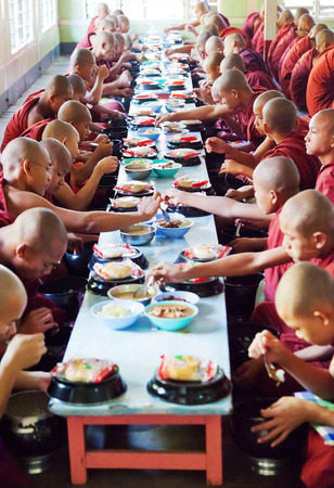 local 27: Mandalay, Myanmar - February 27, 2011: Monks from Mahagandayone monastery eating their morning meal which is food prepared from the local people in the village