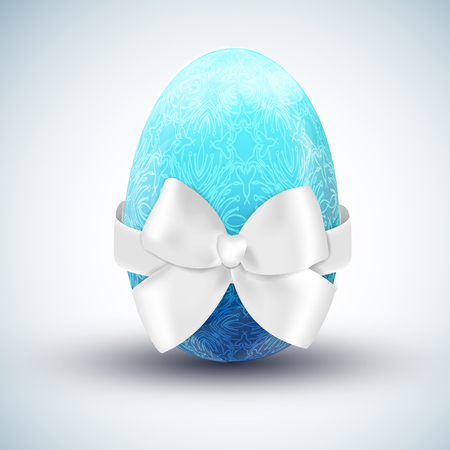 Blue patterned egg with a white bow on a white background