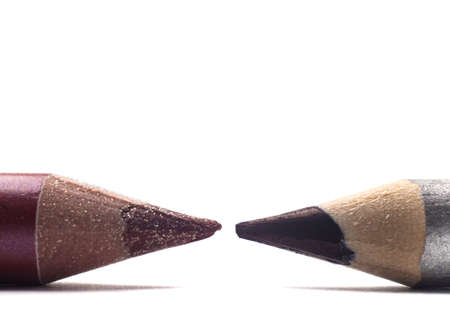 Two cosmetic pencils face off on white photo