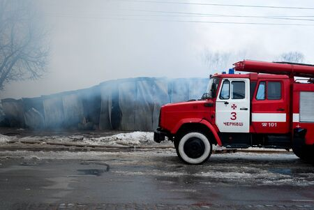 Fire Engine with sirens and blue lights with fire on background.