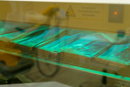 Medical instruments being sterilized under a blue UV Ultra Violate light in a hospital 写真素材